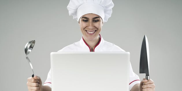 happy woman chef looking at the laptop computer with knife and ladle in her hands