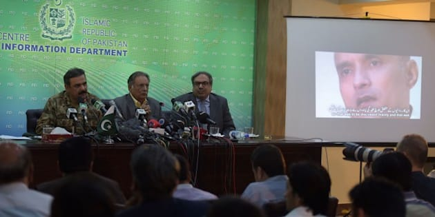 Pakistani Lieutenant General Asim Bajwa (L) speaks with media representatives as he gives details of arrested man Kulbhushan Yadav (R on screen), who is suspected of being an Indian spy, during a press conference in Islamabad on March 29, 2016. Pakistan protested to India after arresting a man suspected of being an Indian spy, sparking a new diplomatic tiff between the nuclear-armed neighbours. The man was arrested during a raid in the southwestern province of Balochistan, Pakistani media reports said quoting local security officials, calling him an agent with India's Research and Analysis Wing (RAW) intelligence agency. / AFP / AAMIR QURESHI        (Photo credit should read AAMIR QURESHI/AFP/Getty Images)