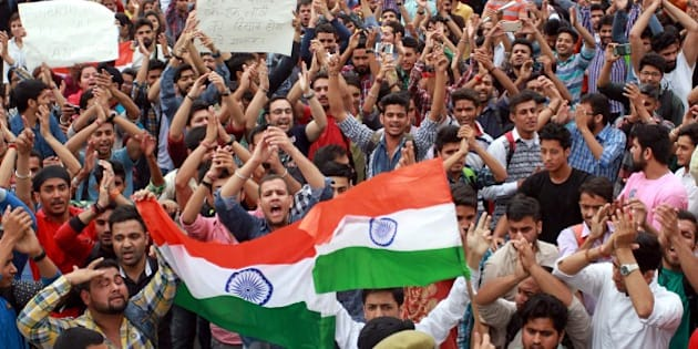 JAMMU, INDIA - APRIL 6: University students holding national flag as they shout slogans during a protest against ongoing unrest at the National Institute of Technology (NIT) in Srinagar, on April 6, 2016 in Jammu, India. Trouble erupted at the NIT after India lost the World T20 semi-final match to West Indies on March 31. Some engineering students from outside the state claimed Kashmiri students had chanted anti-India slogans and burst firecrackers after India lost. (Photo by Nitin Kanotra/Hindustan Times via Getty Images)