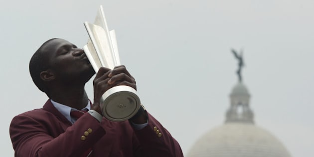 TOPSHOT - West Indies's captain Darren Sammy poses for a photograph with the World T20 cricket tournament trophy one day after West Indies won the event in the Indian city of Kolkata on April 4, 2016. / AFP / Dibyangshu SARKAR        (Photo credit should read DIBYANGSHU SARKAR/AFP/Getty Images)