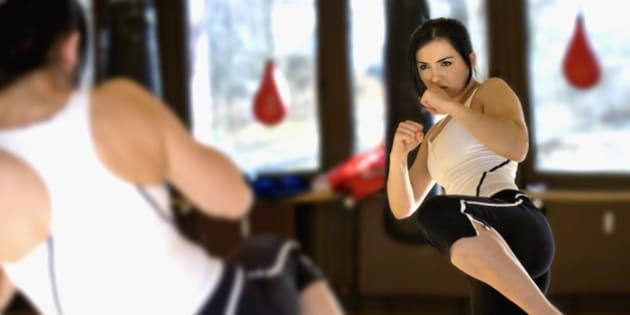 young woman doing kickboxing exercise in front of mirror