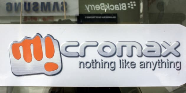 A MicroMax Informatics Ltd. logo is displayed on a store window reflecting Samsung Electronics Co. and Research In Motion Ltd. Blackberry logos from across the street in New Delhi, India, on Tuesday, April 9, 2013. Apple Inc. and Samsung Electronics Co. are being outpaced in the fast-growing Indian smartphone market by aggressive local competitors Micromax and Karbonn Mobiles India Pvt. Ltd. Photographer: Prashanth Vishwanathan/Bloomberg via Getty Images