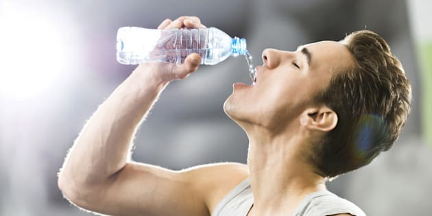 Thirsty young man drinking water after exercising.