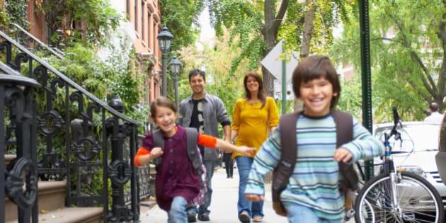 Children running ahead of parents on sidewalk, Manhattan, New York City