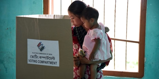 An Indian voter holds a child as she casts her ballot in the state assembly elections at a polling station in Diphu in the Karbi Anglong district some 215kms from Guwahati on April 4, 2016. 
