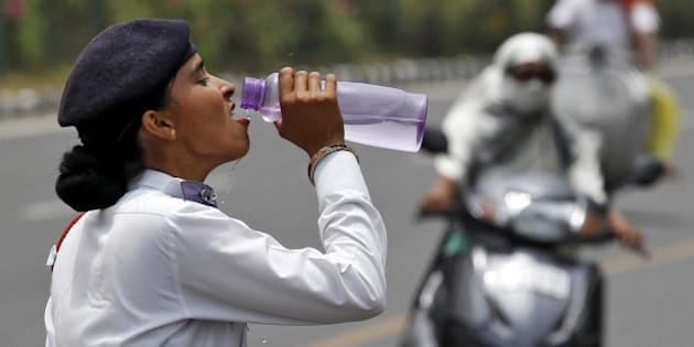 A traffic police woman drinks water as commuters drive along a road on a hot summer day in Chandigarh, India, May 31, 2015. While temperatures regularly top 40 degrees Celsius (104 degrees Fahrenheit) in May and June, parts of the south and east of India have baked under heat as high as 47 degree Celsius for seven straight days.  REUTERS/Ajay Verma
