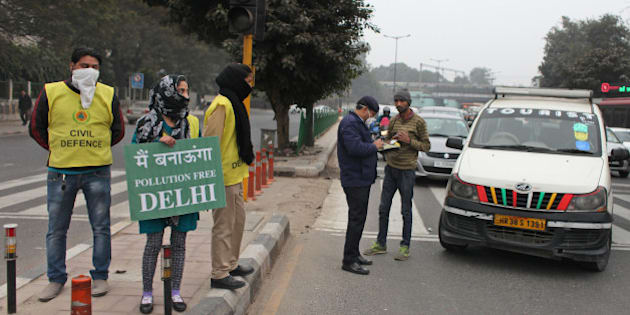 "A volunteer holds a placard which read: ""We will make a pollution free Delhi"" as an Indian traffic policeman checks the papers of a driver at a traffic intersection on the last day of a two-week experiment to reduce the number of cars to fight pollution  in New Delhi, India, Friday, Jan. 15, 2016. To reduce pollution in one of the most polluted cities in the world, the Delhi government allowed private cars on the roads on alternate days from Jan. 1-15, depending on whether their license plates end in an even or an odd number. (AP Photo/Altaf Qadri)"