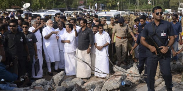 Indian Prime Minister Narendra Modi, second left, wearing white, visits the site after a massive fire broke out during a fireworks display at the Puttingal temple complex in Paravoor village, north of Thiruvananthapuram, southern Kerala state, India, Sunday, April 10, 2016. Dozens were killed and many more were injured when a spark from an unauthorized fireworks show ignited a separate batch of fireworks that were being stored at the temple complex, officials said. Most of the people died when the building where the fireworks were stored collapsed, said Chief Minister Oommen Chandy, the state's top elected official.(Press Trust of India via AP)INDIA OUT