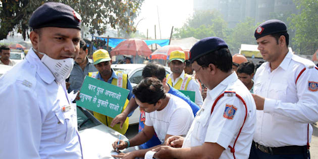 GHAZIABAD, INDIA - APRIL 15: Traffic policemen issue a challan to a commuter for driving an even-number vehicle during the 1st day of the second phase of the odd-even scheme at Delhi-Ghaziabad border, on April 15, 2016 in Ghaziabad, India. More than 500 people were challaned by Delhi Traffic Police for violating the odd-even norms in the first five hours of the second phase of the road-rationing formula implemented in the national capital on Friday. The scheme was rolled out in Delhi for the second time with chief minister Arvind Kejriwal appealing to the people of the city to join hands and make the road-rationing plan a success. The Aam Aadmi Party government implemented the first phase of the radical initiative between January 1 and 15 to clean up Delhis toxic air, considered the worst in the world. (Photo by Sakib Ali/Hindustan Times via Getty Images)