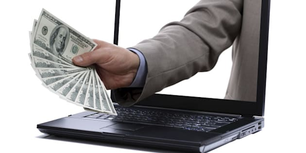Holding one hundred dollar bills through a laptop screen concept for internet e-commerce, paying and electronic banking