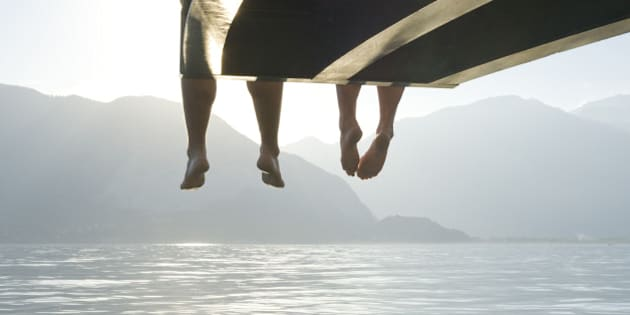 Couple's feet dangle from end of lake wharf