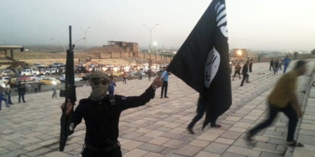 A fighter of the Islamic State of Iraq and the Levant (ISIL) holds an ISIL flag and a weapon on a street in the city of Mosul, June 23, 2014. U.S. Secretary of State John Kerry held crisis talks with leaders of Iraq's autonomous Kurdish region on Tuesday urging them to stand with Baghdad in the face of a Sunni insurgent onslaught that threatens to dismember the country. Picture taken June 23, 2014. REUTERS/Stringer (IRAQ - Tags: CIVIL UNREST POLITICS TPX IMAGES OF THE DAY)