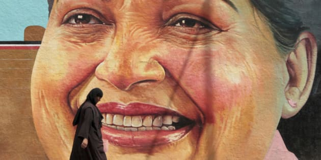 A woman walks past a portrait of J. Jayalalithaa, Chief Minister of the southern Indian state of Tamil Nadu, in Chennai March 13, 2012. REUTERS/Babu (INDIA - Tags: POLITICS SOCIETY)
