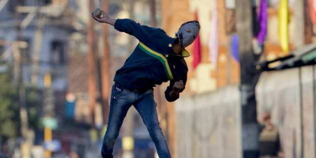 A Kashmiri masked Muslim protester throws rocks at Indian policemen during a protest in Srinagar, Indian controlled Kashmir, Tuesday, April 12, 2016. Two young men were killed in firing by Indian government forces at rock-throwing protesters in the town of Handwara around 80 kilometers (50 miles) north of here on Tuesday, police said. (AP Photo/Dar Yasin)