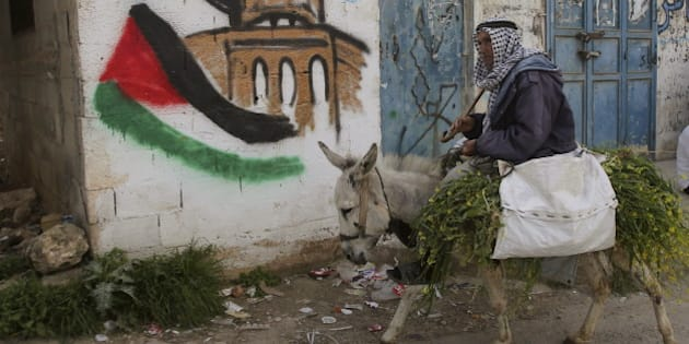 A Palestinian villager rides his donkey past a mural in the West Bank village of Awarta near Nablus March 19, 2015. REUTERS/Abed Omar Qusini