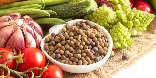 Raw organic roveja beans and vegetables isolated on white