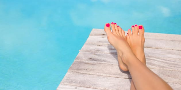 Bare woman feet on wooden deck by the swimming pool.