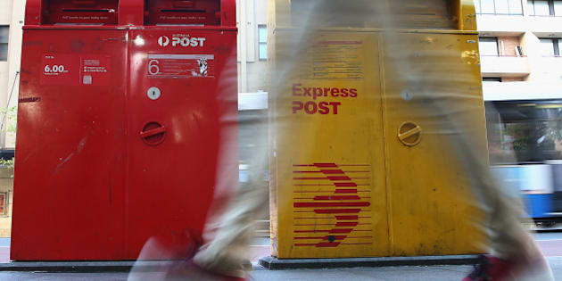 SYDNEY, AUSTRALIA - MAY 07:  A man scuttles past a Post Office Box outside the Darlinghurst Post Office on May 7, 2014 in Sydney, Australia. Australia Post is considering a user-pay mail delivery model as letter operations saw a AUD $218 million loss last year.  (Photo by Don Arnold/Getty Images)