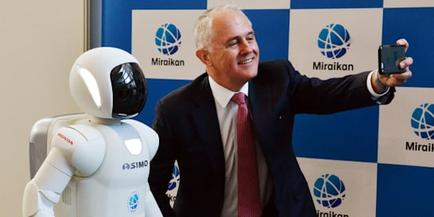 Australian Prime Minister Malcolm Turnbull (R) takes a selfie with Japanese auto giant Honda Motor's humanoid robot Asimo (L) at the National Museum of Emerging Science and Innovation in Tokyo on December 18, 2015. Turnbull is on a one-day visit to Tokyo and will have talks with Japanese counterpart Shinzo Abe. AFP PHOTO / POOL / Yoshikazu TSUNO / AFP / POOL / YOSHIKAZU TSUNO        (Photo credit should read YOSHIKAZU TSUNO/AFP/Getty Images)