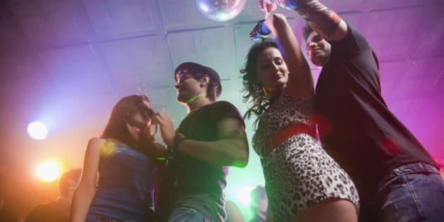 Two young couples on nightclub dance floor