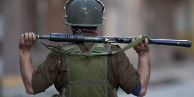 An Indian policeman looks from distance as they clash with Kashmiri Muslim protesters during a protest in Srinagar, Indian controlled Kashmir, Tuesday, April 12, 2016. Two young men were killed in firing by Indian government forces at rock-throwing protesters in the town of Handwara around 80 kilometers (50 miles) north of here on Tuesday, police said. (AP Photo/Dar Yasin)
