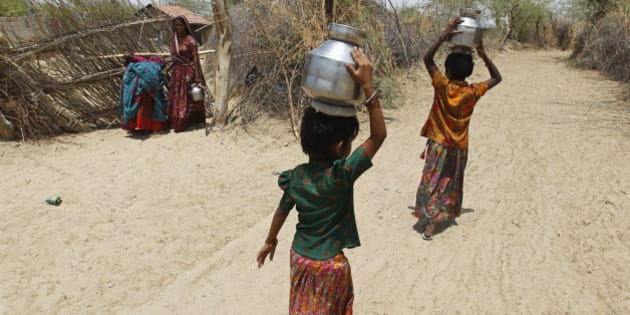 Village girls carry metal pitchers filled with water supplied by the government in the western Indian state of Gujarat April 23, 2013. India may be heading for another bumper grain harvest, if the first forecast for this year's monsoon proves correct, but the rain may be too little - and too late - for southern and western states already parched by the worst drought in four decades. REUTERS/Amit Dave (INDIA - Tags: SOCIETY ENVIRONMENT DISASTER BUSINESS)