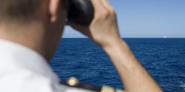 Officer looks through binoculars with cruise ship in distance, near Mozambique, Indian Ocean.