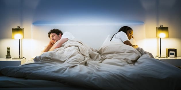 Multi-ethnic couple ignoring each other while lying in bed at home