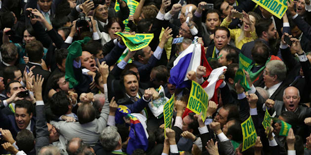 Opposition lawmakers celebrate after the lower house of Congress voted to impeach Brazil's President Dilma Rousseff in the Chamber of Deputies in Brasilia, Brazil, Sunday, April 17, 2016. The measure now goes to the Senate. Rousseff is accused of using accounting tricks in managing the federal budget to maintain spending and shore up support. (AP Photo/Eraldo Peres)
