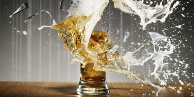 Glass of beer shattering on table surface