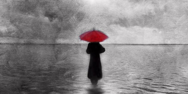 Atmospheric solitary woman with red umbrella wading in water