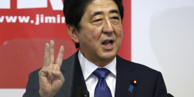 "Japanese Prime Minister Shinzo Abe explains about ""three arrows"" of his ""Abenomics"" plan during a press conference at the headquarters of his ruling Liberal Democratic Party in Tokyo, Thursday, Sept. 24, 2015.  Prime Minister Abe, fresh from a bruising battle over unpopular military legislation, announced Thursday an updated plan for reviving the world's third-largest economy, setting a GDP target of 600 trillion yen ($5 trillion).(AP Photo/Shuji Kajiyama)"