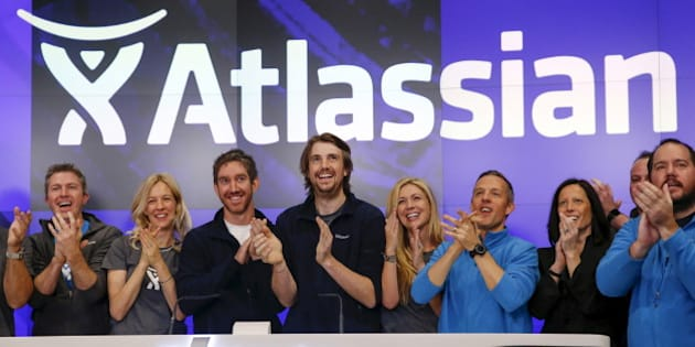 Mike Cannon-Brookes (C), co-founder and CEO of Atlassian Software Systems, and Scott Farquhar (3rd L), co-founder and CEO of Atlassian Software Systems, smile during it's opening PO at the Nasdaq at a MarketSite in New York, December 10, 2015. Atlassian Corporation Plc raised $462 million in its initial public offering in New York on Wednesday, as investors gave the Australian software company a warmer reception versus other stock market hopefuls in the technology sector this year. REUTERS/Shannon Stapleton