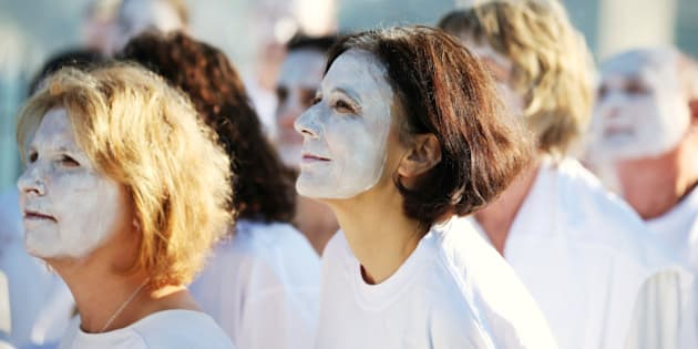 Demonstrators from the environmental group Greenpeace paint their faces white to highlight coral bleaching in Sydney, Friday, April 22, 2016. The group are attempting to raise concerns of climate change when as many as 170 countries are expected to sign the Paris Agreement on climate change as the landmark deal takes a key step toward entering into force years ahead of schedule. (AP Photo/Rick Rycroft)