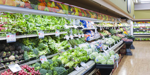 Vegetables are stacked across a supermarket shelf.