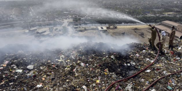NEW DELHI, INDIA - APRIL 21: Firemen trying to douse fire at Delhi's largest landfill Bhalswa dump yard due to soaring temperature on April 21, 2016 in New Delhi, India. A large cloud of smoke was emanating from the landfill as fire tenders were dousing the fire. The 40 acre-wide trash mountain, receives about 2,700 tonnes of garbage per day. The dump yard receives garbage from no less than 50 per cent of Delhi's population, including Civil Lines, Jahangirpuri, Model Town, Kirti Nagar and even old Delhi's Chandni Chowk.   (Photo by Ravi Choudhary/Hindustan Times via Getty Images)