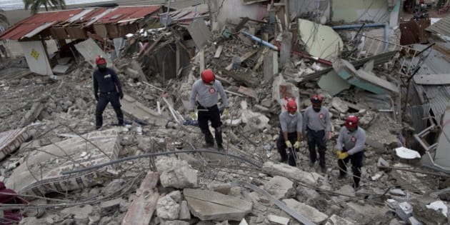 Ecuadorean firefighters comb through rubble of buildings destroyed by a 7.8-magnitude earthquake, in Pedernales, Ecuador, Friday, April 22, 2016. Rescuers continued to comb through the rubble in coastal towns hit hardest by the quake, but the clock was running down for finding survivors. Rescue workers have said a person without serious injuries can survive up to a week buried in debris in the Ecuadorian heat. (AP Photo/Rodrigo Abd)
