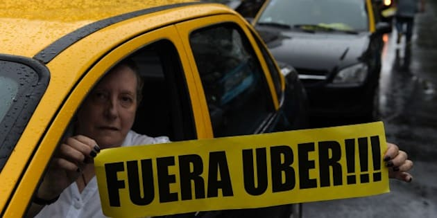 A taxi driver holds a banner reading in Spanish 'Get out Uber' while cabs block Callao avenue, during a protest against Uber in Buenos Aires on April 15, 2016.  Uber started operating in Buenos Aires on April 12 without official permission, unleashing a war with taxi drivers who blocked avenues in protests that caused traffic chaos.  / AFP / Juan Mabromata        (Photo credit should read JUAN MABROMATA/AFP/Getty Images)