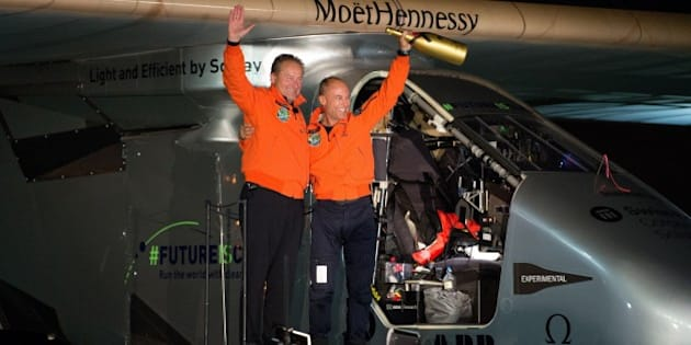 Swiss adventurer Bertrand Piccard (R) and Andre Borschberg (L) wave to the crowd after landing Solar Impulse 2 at Moffett Field in Mountain View, California on April 23, 2016.    Solar Impulse 2, an experimental plane flying around the world without consuming a drop of fuel, landed in California, one leg closer to completing its trailblazing trip. / AFP / Josh Edelson        (Photo credit should read JOSH EDELSON/AFP/Getty Images)