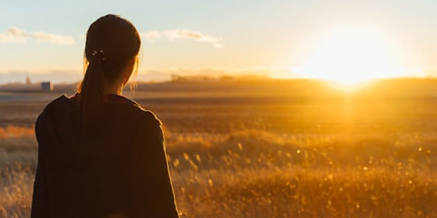 A Japanese woman is standing in a grassy field seeing the sunset in the distance.