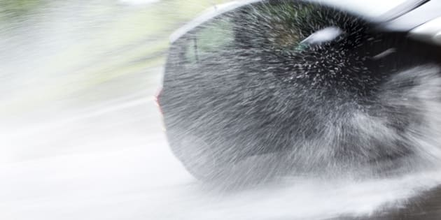 A car sprays a fountain of water as it drives through a large puddle in heavy rain in Berlin, Germany, Saturday, July 14, 2012. A weekend with a mix of sun and rain with the possibility of thunderstorms is forecasted for large parts of Germany. (AP Photo/Gero Breloer)