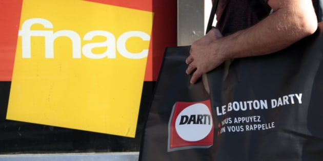 A picture illustration shows a man holding a bag of electrical goods retailer Darty as he stands near a store window with a logo of French music retailer Fnac in Nice, France, November 6, 2015. Books and music retailer Fnac said on Friday that it had raised its offer for electrical goods company Darty in an agreed deal that would create a French market leader in white goods. The companies said in a statement that the new offer of about 116 pence per Darty share, up from 101 pence, valued Darty at about 615 million pounds ($934 million), against 533 million previously.   REUTERS/Eric Gaillard