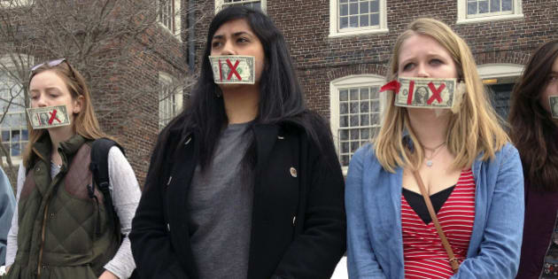 Brown University senior Maahika Srinivasan, center, of New Delhi, India, stands with senior Jeanette Sternberg Lamb, right, of Asheville, N.C., Wednesday, March 11, 2015, on the campus in Providence, R.I., where they organized a march to protest how the college handled recent sexual assault allegations. (AP Photo/Amy Anthony)