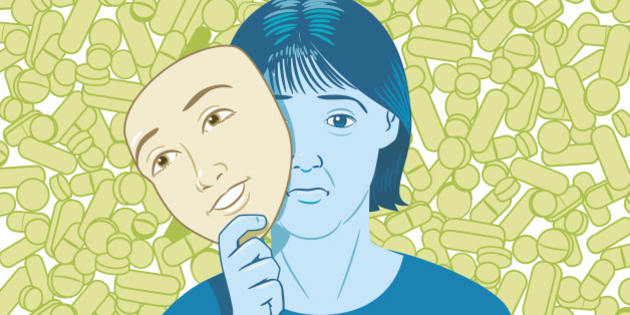 Lots of pills behind woman holding happy mask disguising sad face