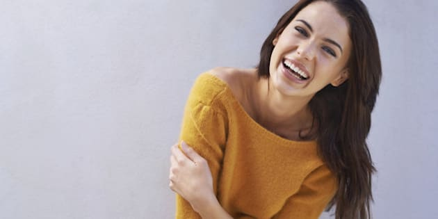 Portrait of a beautiful young woman laughing while standing against a gray wall