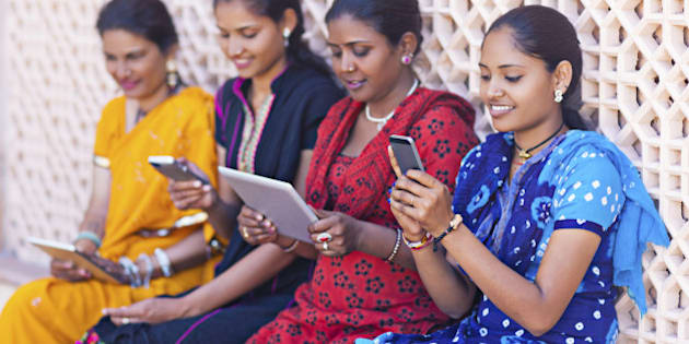 Four indian women playing with digital tablets and smart phones.