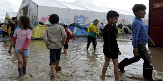 Children play in a puddle following heavy rainfall at a makeshift camp for migrants and refugees at the Greek-Macedonian border near the village of Idomeni, Greece, April 24, 2016. REUTERS/Alexandros Avramidis