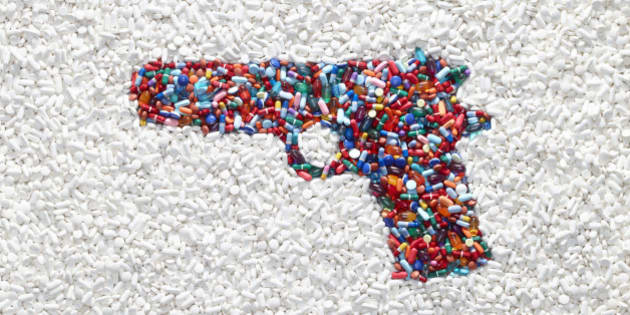 A handgun formed by colored pills surrounded by white pills