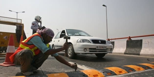 NEW DELHI, INDIA � AUGUST 1: Workers install a metallic speed breaker on the Dwarka flyover after 9 people lost their lives on the flyover due to the faulty design of the flyover in New Delhi on Saturday, August 1, 2009. (Photo by Shekhar Yadav/ India Today Group/ Getty Images)