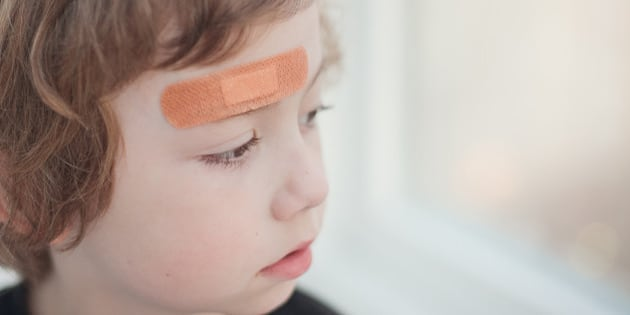 portrait of a boy with a band aid in  his forehead